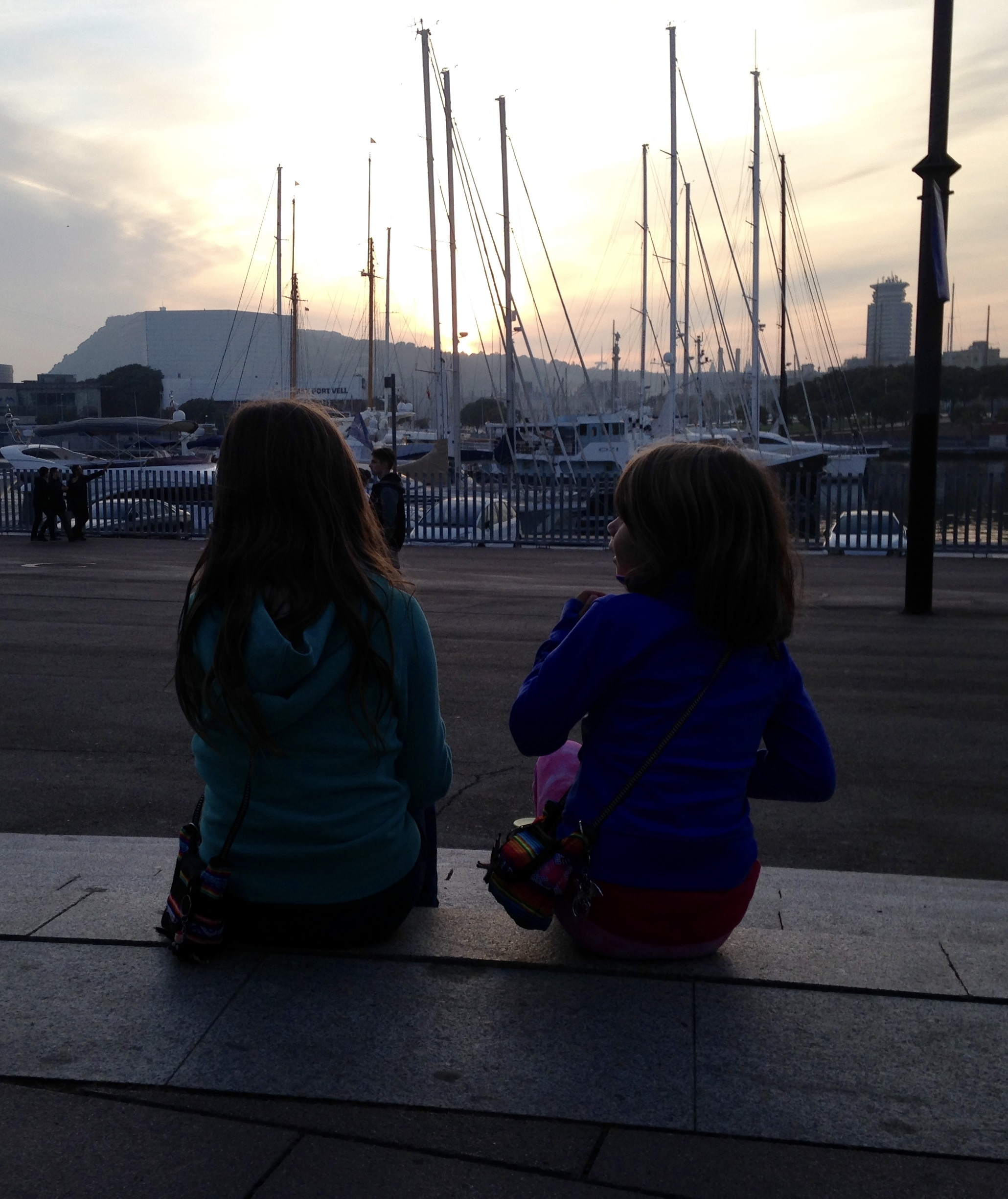 Mackenzie and Quinn sit on concrete stairs in front of the marina at sunset