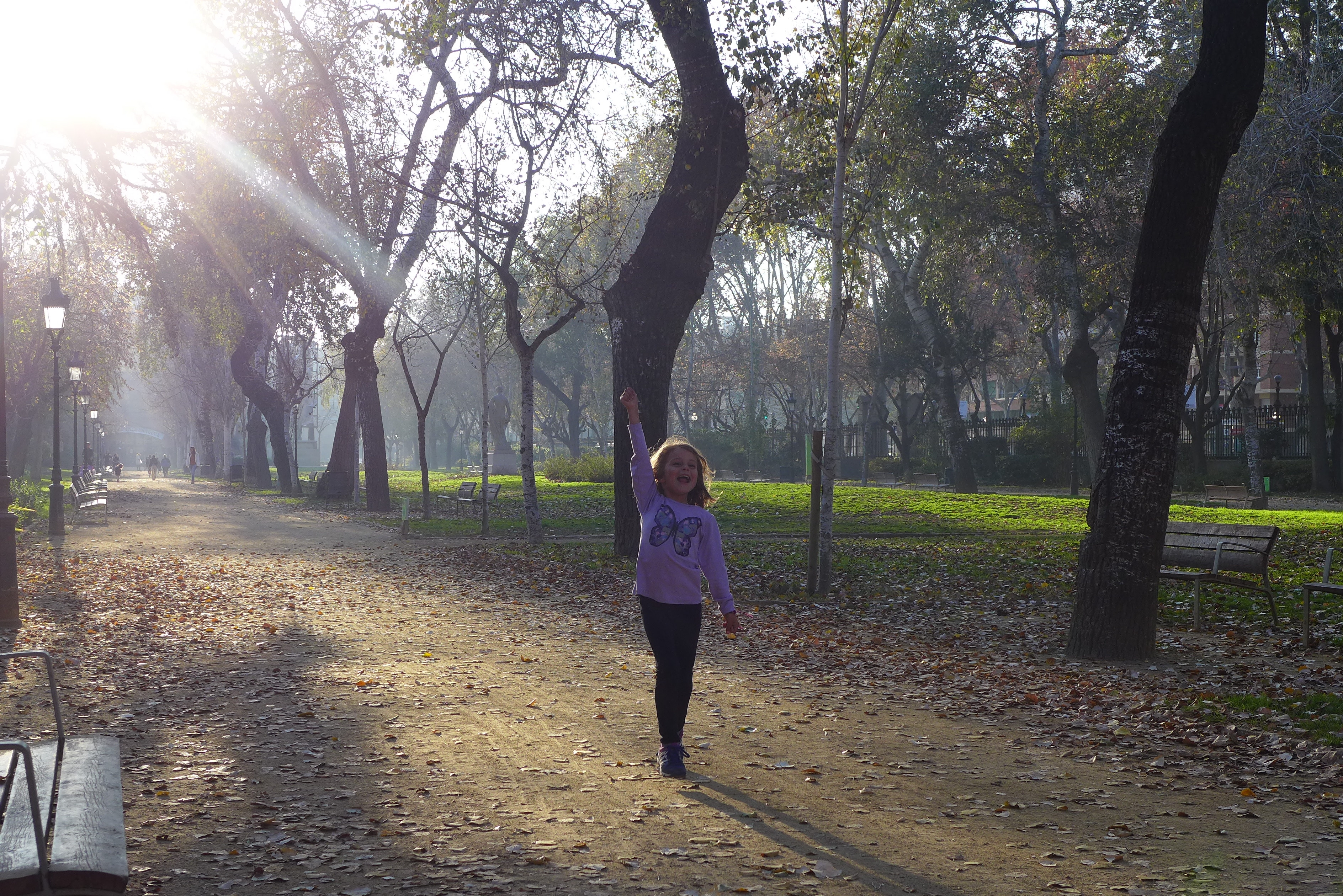 Quinn running through a park with her hand in the air