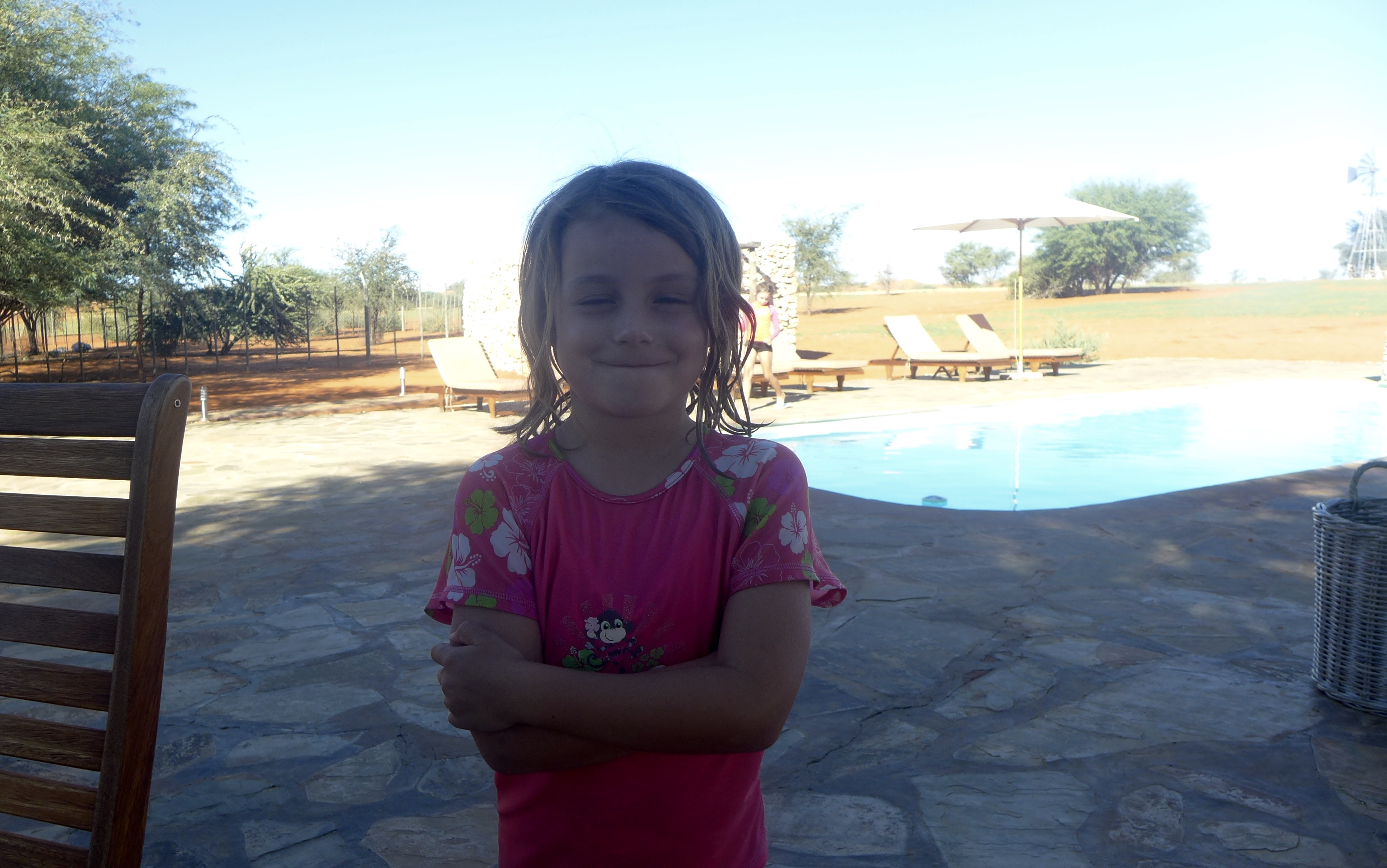 Quinn in a swimsuit stands in front of a pool with arms crossed a smirk on her face