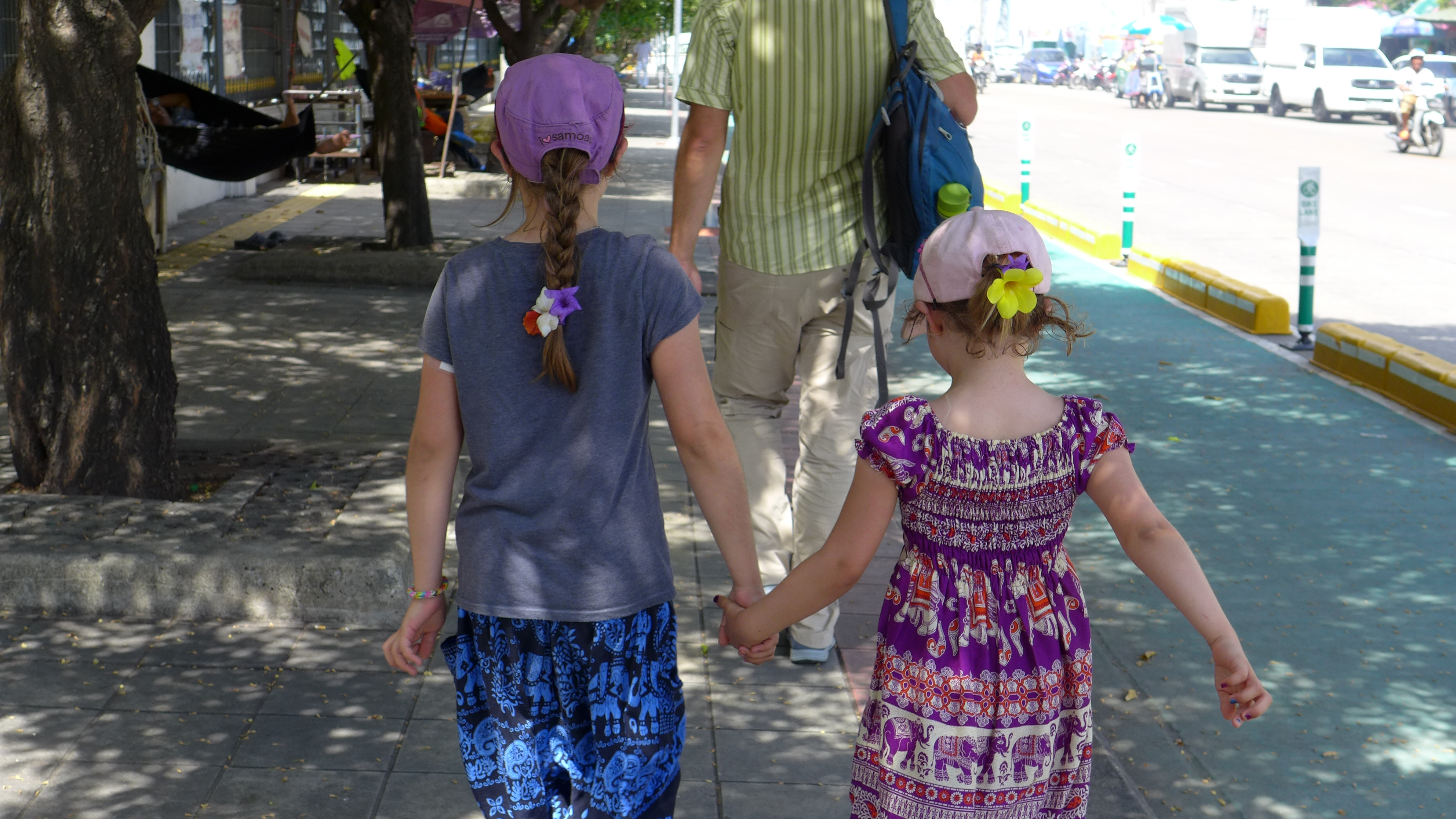 Quinn and Mackenzie hold hands with flowers in their hair walking behind Jacob